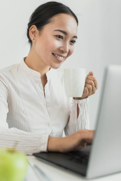 Mujer de negocios, sonriente, en, computador portatil Foto gratis