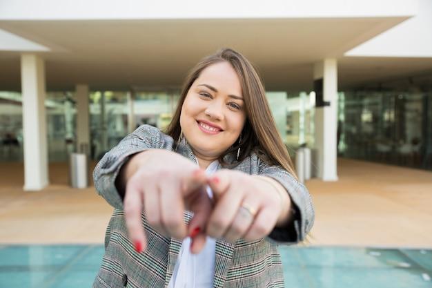 Mujer de negocios sonriente que señala los dedos en la cámara al aire libre Foto gratis