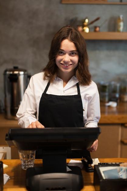Mujer de negocios sonriente trabajando en cajero Foto gratis