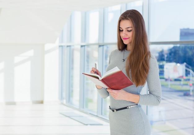 Mujer de negocios sosteniendo un diario en sus manos, mirándolo y tomando notas con un bolígrafo Foto Premium
