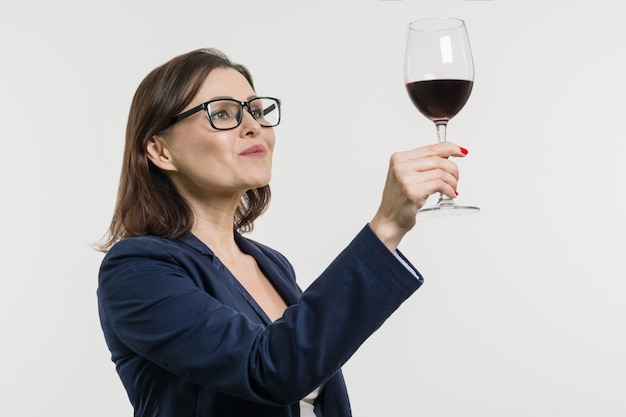 La mujer de negocios está sosteniendo y está mirando un vidrio de vino rojo. Foto Premium