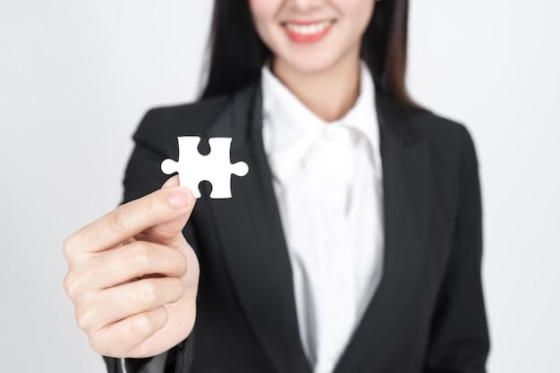 Mujer de negocios sosteniendo y mostrando un rompecabezas Foto gratis