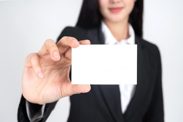 Mujer de negocios sosteniendo y mostrando tarjeta vacía o tarjeta de presentación Foto gratis