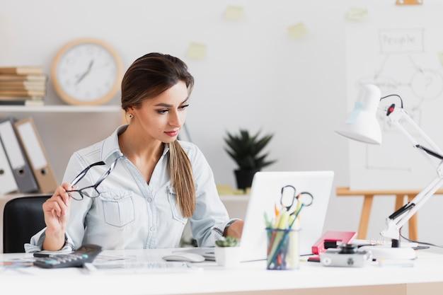 Mujer de negocios sosteniendo sus gafas y trabajando en la computadora portátil Foto gratis