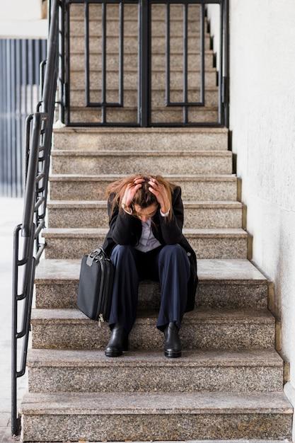 Mujer de negocios subrayada que se sienta en las escaleras Foto gratis