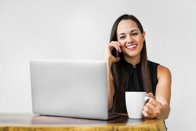 Mujer de negocios con una taza de café hablando por teléfono Foto gratis