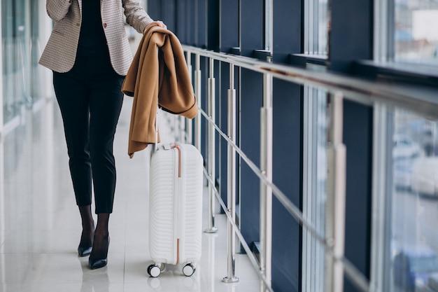 Mujer de negocios en terminal con bolsa de viaje Foto gratis