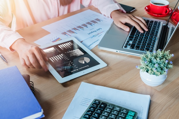 Mujer de negocios trabajando con tableta digital y libro y documento en el escritorio de madera en la moderna Foto Premium