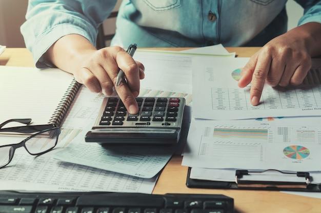 Mujer de negocios usando la calculadora para calcular la ...