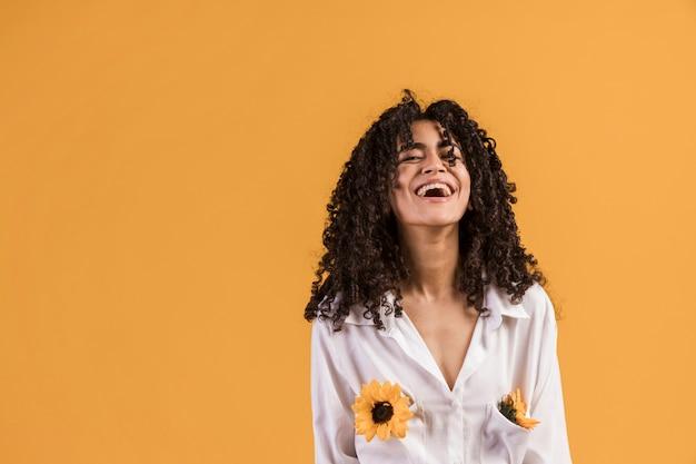 Mujer negra con flores en bolsillos de camisa riendo. Foto gratis