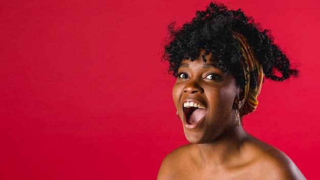 Mujer negra joven desnuda sorprendida en estudio con el fondo brillante Foto gratis