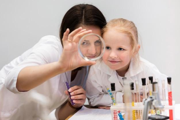 Mujer y niña mirando a través de la lupa Foto gratis