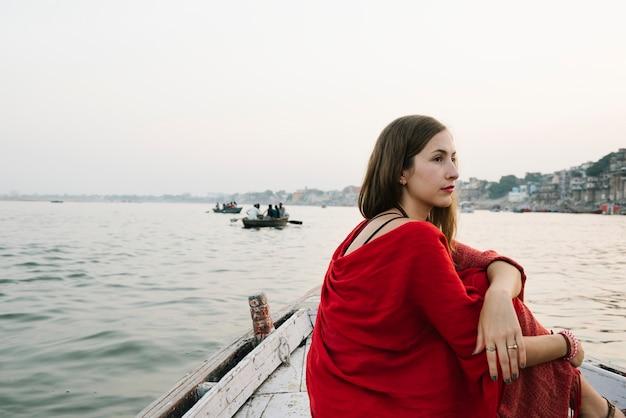 Mujer occidental en un barco explorando el río ganges Foto gratis