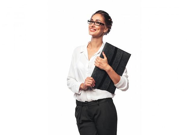 Mujer de oficina joven bastante rubia abrazando una carpeta de documentos gris y sonriendo Foto Premium