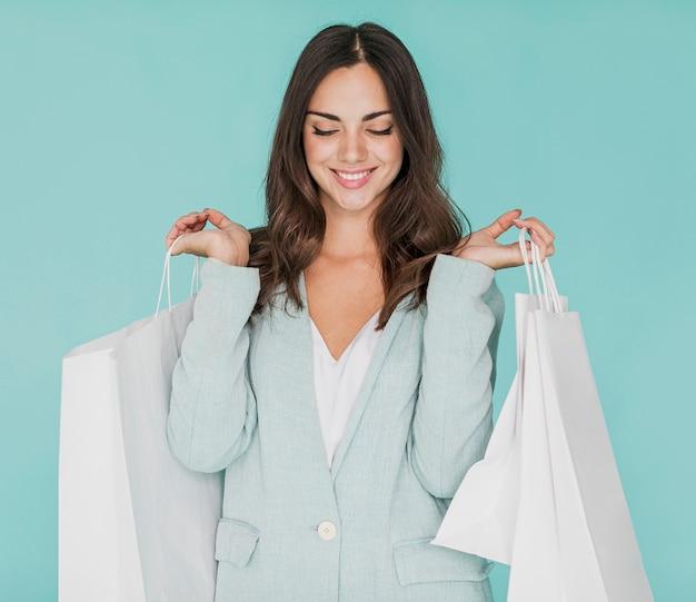 Mujer con los ojos cerrados y bolsas de compras en ambas manos. Foto gratis