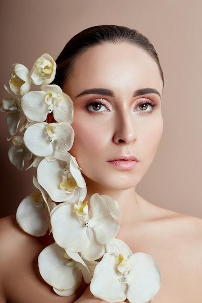 Mujer con orquídea blanca cerca de maquillaje de niña de cara Foto Premium
