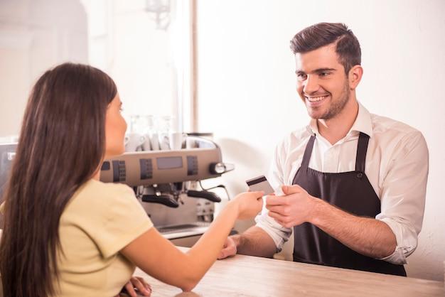 La mujer está pagando el café con tarjeta de crédito. Foto Premium