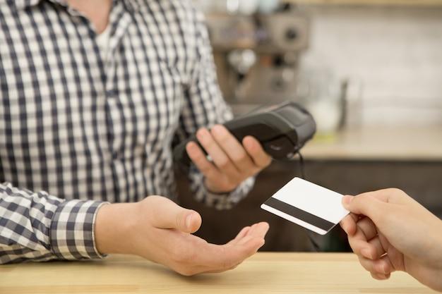 Mujer pagando con tarjeta de crédito en la cafetería. Foto Premium