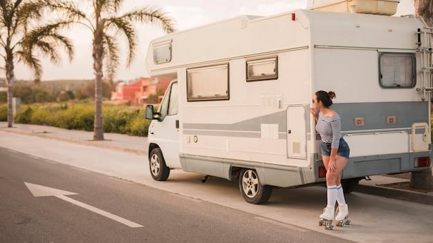 Mujer patinadora de pie detrás de la caravana en la carretera mirando a escondidas Foto gratis
