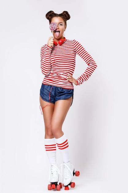 Mujer en patines y con auriculares rojos y piruleta Foto Premium
