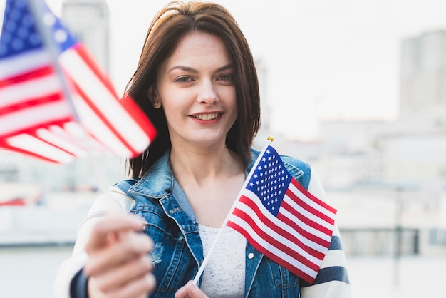 Mujer patriótica feliz mostrando banderas americanas Foto gratis