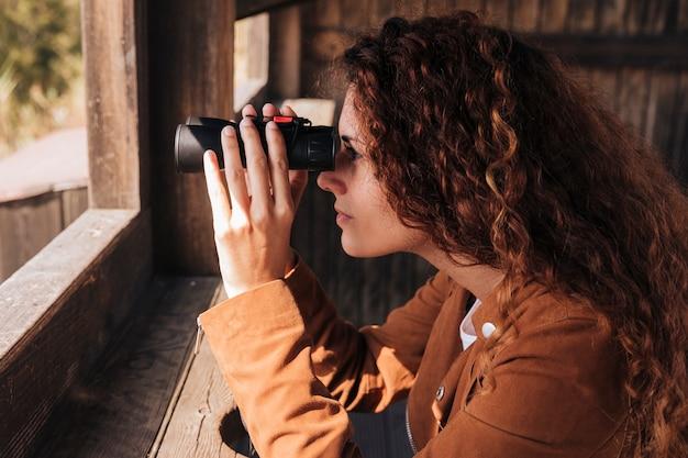 Mujer pelirroja de lado mirando a través de binoculares Foto gratis