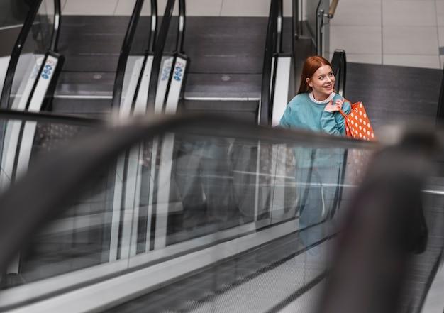 Mujer pelirroja subir escaleras mecánicas Foto gratis