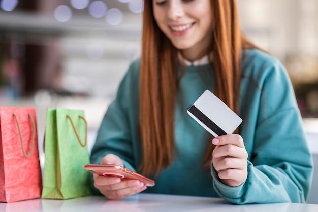 Mujer pelirroja con teléfono y tarjeta de crédito Foto gratis