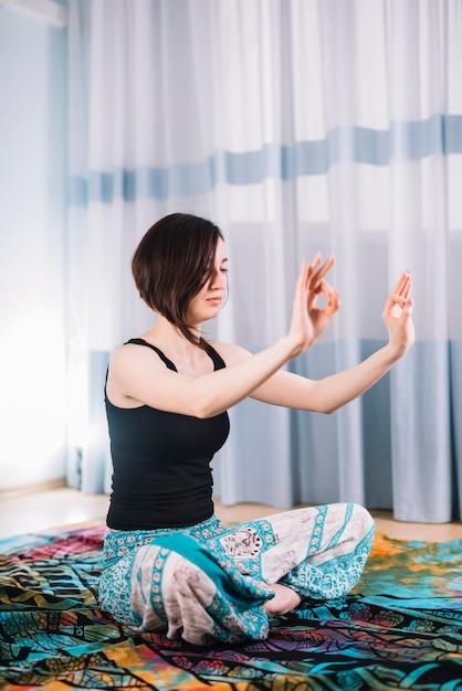 Mujer de pelo corto meditando con gesto de gyan mudra Foto gratis