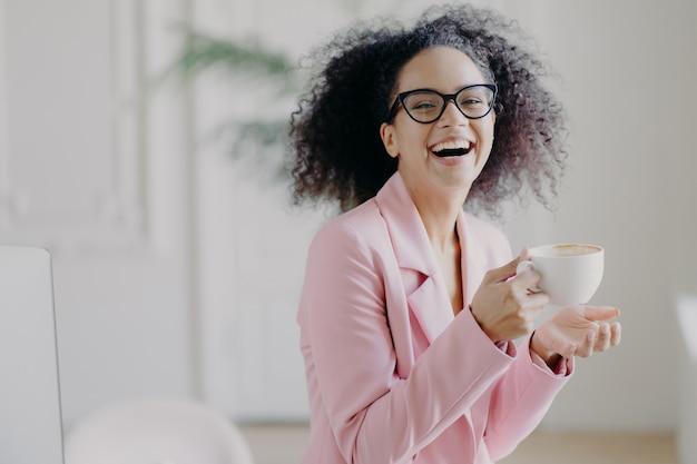 Mujer de pelo rizado muy contenta ríe alegremente mientras bebe café caliente Foto Premium