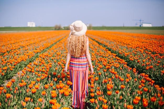 Mujer con el pelo rojo largo que lleva un vestido rayado que hace una pausa la parte posterior en campo colorido del tulipán. Foto Premium