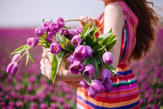 Mujer con el pelo rojo largo que lleva un vestido rayado que sostiene una cesta con el ramo de flores de tulipanes púrpuras Foto Premium