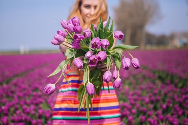 Mujer de pelo rojo que lleva un vestido que sostiene una cesta con el ramo de flores de tulipanes Foto Premium