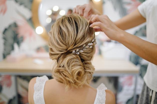 Mujer de peluquería tejiendo trenzas, peinado de boda. Foto gratis