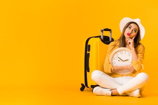 Mujer pensando mientras sostiene el reloj junto al equipaje con espacio de copia Foto gratis