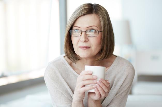Mujer pensando con una taza de té Foto gratis