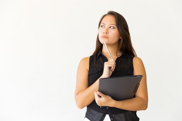 Mujer pensativa con carpeta y bolígrafo Foto gratis