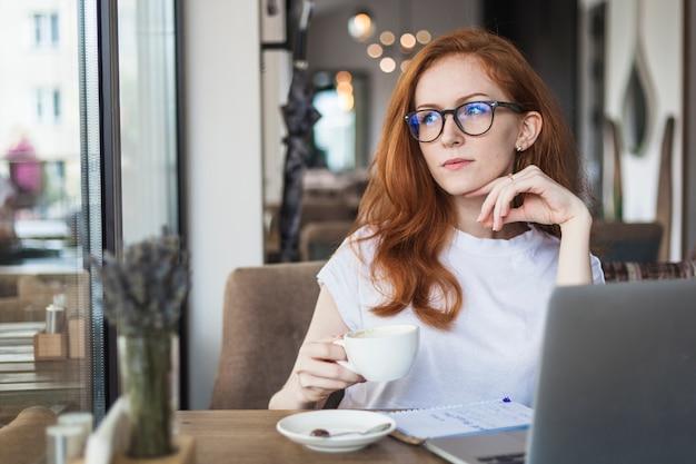Mujer pensativa con taza de café Foto gratis