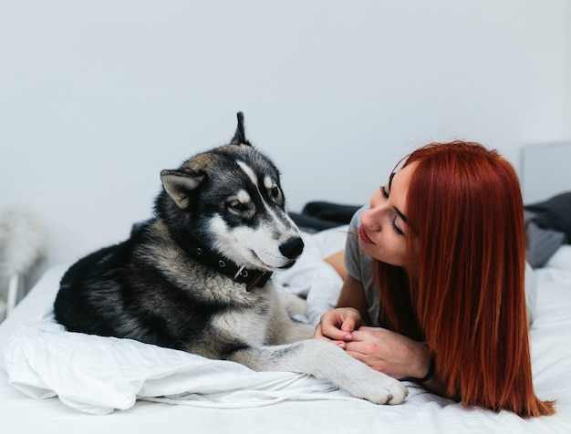 Mujer con perro grande en la cama   Foto Gratis