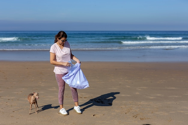 Mujer con perro recogiendo basura y plásticos limpiando la playa Foto Premium