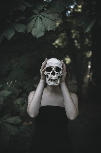Mujer de pie con calavera en el matorral durante el día Foto gratis