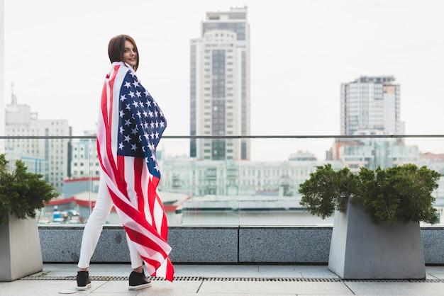 Mujer de pie en media vuelta con gran bandera de estados unidos Foto gratis