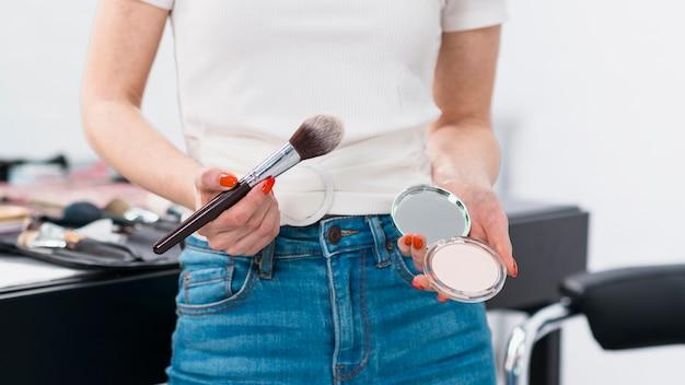 Mujer de pie con pincel y polvo Foto gratis