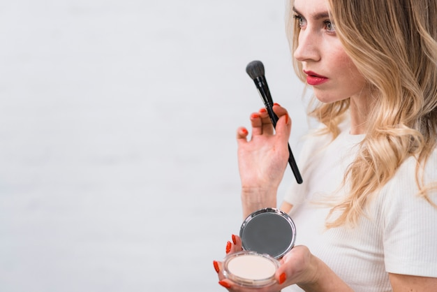 Mujer de pie, con, polvo, y, cepillo Foto gratis