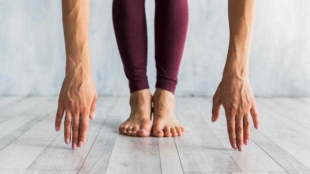 Mujer de pie en una pose de flexión hacia adelante Foto gratis