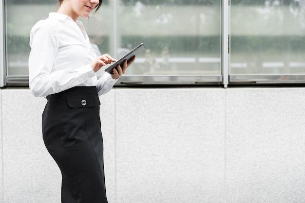 Mujer de pie de primer plano con tableta Foto gratis