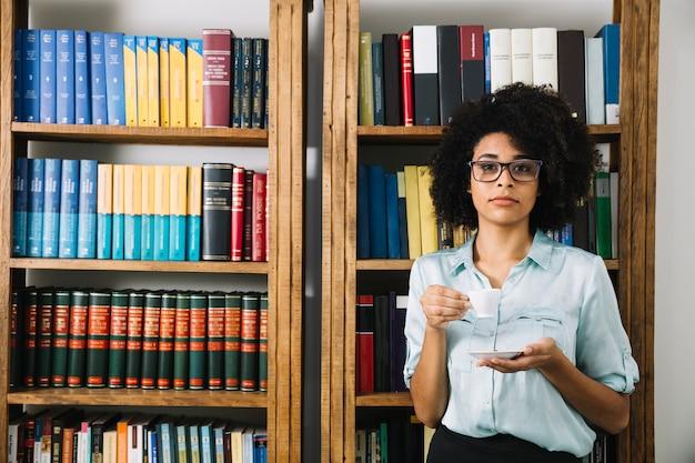 Mujer de pie con una taza de café en la biblioteca Foto gratis