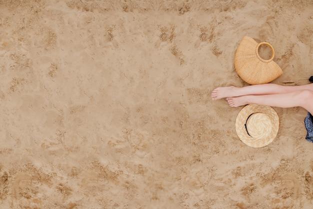 Mujer piernas bronceadas con sombrero de paja y bolsa en la playa de arena Foto Premium