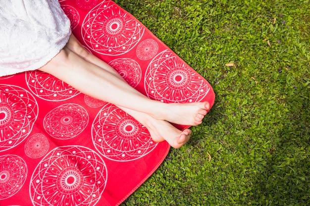 Mujer con las piernas cruzadas sentado en una manta roja sobre la hierba verde Foto gratis