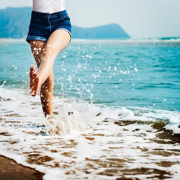 Mujer pies salpicaduras de agua de mar Foto gratis